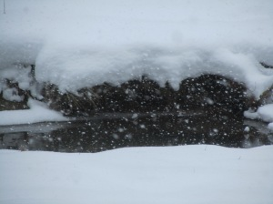 Snow on the side of the creek in front of the Cabin...